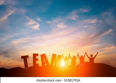 Silhouette of happy business team making high hands in sunset sky background and text TEAM for business teamwork concept