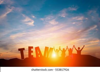 Silhueta de equipe de negócios feliz fazendo mãos altas no fundo do céu do sol e texto EQUIPE para o conceito de trabalho em equipe de negócios