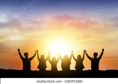 Silhouette of happy business teamwork making high hands over head in sunset sky evening time background as business successful,victory,business teamwork concept and freedom .