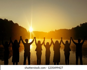 Silhouette of happy business teamwork  making high hands over head in beautiful sunset at  evening time background for teamwork concept and freedom