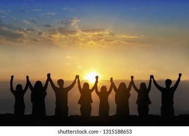 Silhouette of happy business teamwork making high hand over head standing back view  on sunrise background, friendship,victory,achieve target,copy space.