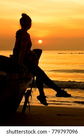 Silhouette of happy carefree woman sitting on the head of boat in the sunrise on the seaside. Relax, freedom and feel free on vacation time. Healthy living  with Summer sport and freedom concept