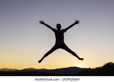 Silhouette of happy child jumping playing on mountain at sunset or sunrise