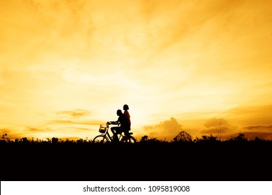 Silhouette happy children riding bicycle and having fun in summer with background the sunrise on the mountain , concept relax time and lifestyle.