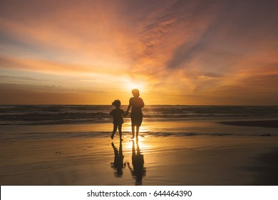 Silhouette of happy children running on the beach while holding hands at sunset time