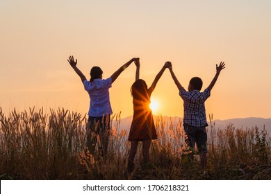 Silhouette of happy children standing with raised hands on the mountain at the sunset time.