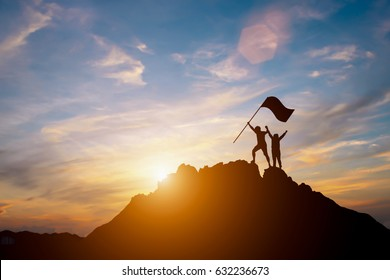 Silhouette of happy climbers  in sunset teamwork concept.