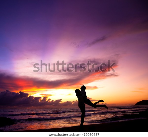 Silhouette of happy  couple embracing on the beach