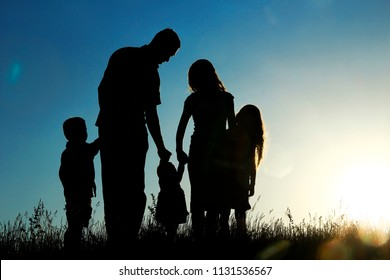 silhouette of a happy family with children on sunset