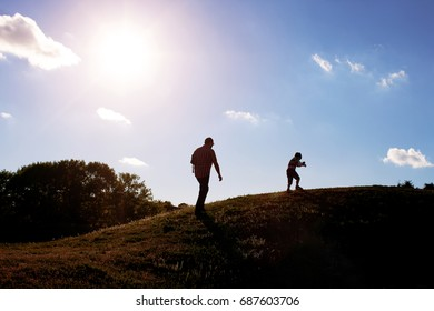 Silhouette, happy family with children playing on meadow, sunset, summertime