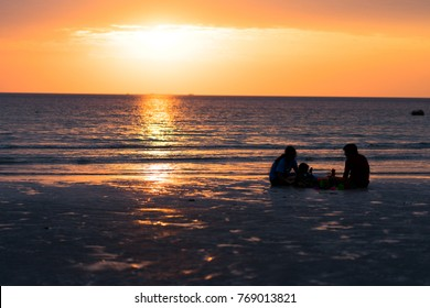 Silhouette happy family enjoying on beach with sunset