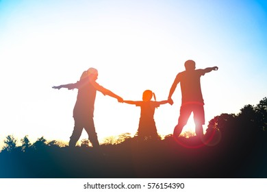 Silhouette of happy family father,mother and daughter in the park at sunset with sun flare