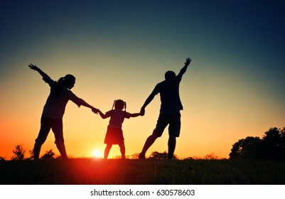Silhouette happy family father,mother and daughterin the park at sunset