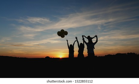 Silhouette: A happy family of four looks at the sunset, raise their hands up. A little son sits on his father's shoulders. Girl holding air balloons in her hand. Rear view