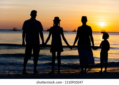 Silhouette of happy family having fun on the beach at the sunset time. Concept of friendship forever and of summer vacation.
