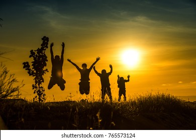 Silhouette of Happy family jumping on the hill. Concept of friendly family and of summer vacation.
