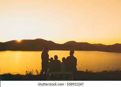 The silhouette of happy family looking sunset