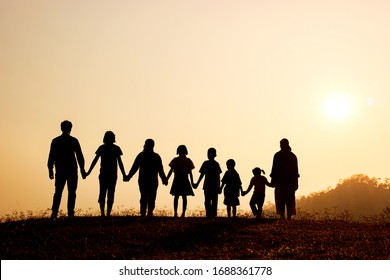 Silhouette of happy family standing on the mountain at the sunset time.