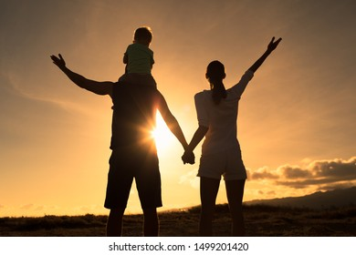 Silhouette of happy family of three with arms up facing sunset.