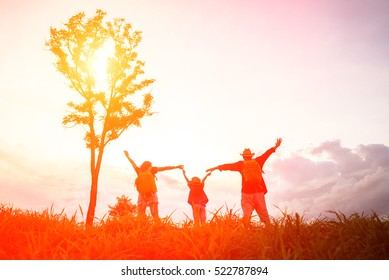 Silhouette of a happy family of three people, mother, father and child in front of a sunset sky.