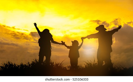 Silhouette happy family .Happy family together, parents with their little child at sunset. Father raising baby up in the air.