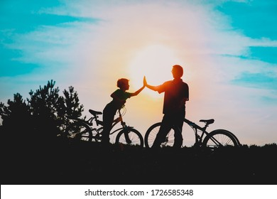 Silhouette of happy father and son biking at sunset