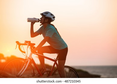 Silhouette of a happy female cyclist in helmet riding her bike and drinking water with sea on background at sunset. Adventures and active lifestyle concept