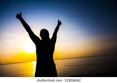 Silhouette of happy female keeping thumbs up on sunset/sunrise seaside background, concept of endurance, strength, success, healthy lifestyle
