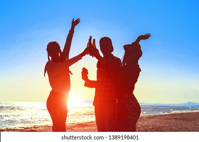 Silhouette of happy friends dance at beach party on sunrise  light - Teenagers cheers with beer bottles having fun  moment on summer holiday - Concept of teenage friendship - Soft bluish filter image
