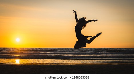 Silhouette of a happy girl jumping in the beach at the sunset. Freedom and leisure vacation concept.