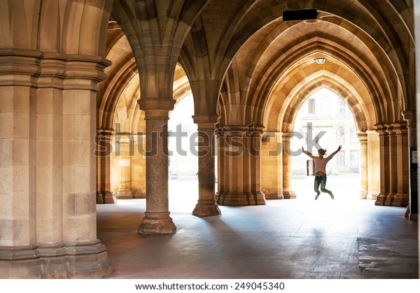 Silhouette of happy girl jumping high up in cloisters of Glasgow University. Scotland. Summertime outdoors.