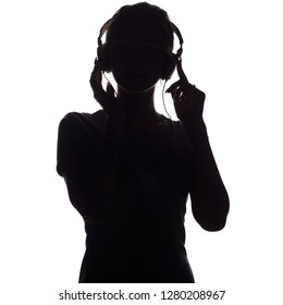 silhouette of a happy girl listening to music in headphones, figure of young woman with hands up relaxing on a white isolated background and and dancing to the music, concept of hobby and leisure