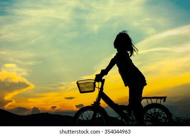 silhouette of a happy girl outside riding  bicycle during sun set.
