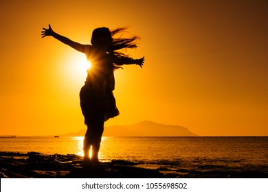silhouette of happy girl standing at the beach against sunrise
