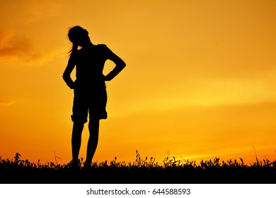 Silhouette of happy girl standing on grass field and sky sunset
