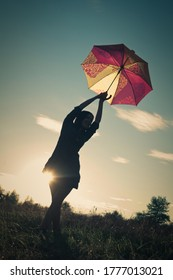 Silhouette of a happy girl with umbrella against sunset sky outside in the fields. painterly sunset