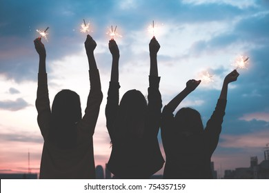 silhouette happy group of asia girl friends enjoy and play sparkler at rooftop party at evening sunset,Holiday celebration festive,teeage lifestyle,freedom and fun