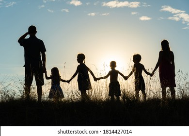 Silhouette of a happy large family at sunset.
