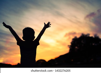 Silhouette of happy little boy with arms raised up facing sunset.