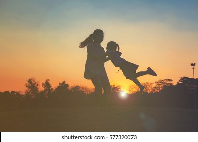 Silhouette of happy little girl child running into arms of his loving mother for hug with sun flare, in front sunset in the sky on Chatuchak Park at Bangkok City, Thailand. Concept of friendly family.