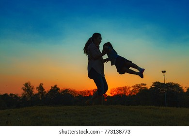 Silhouette of a happy little girl child running into the arms of his loving mother for a hug, in front of the sunset in the sky on a summer day at Bangkok City, Thailand. Concept of friendly family.