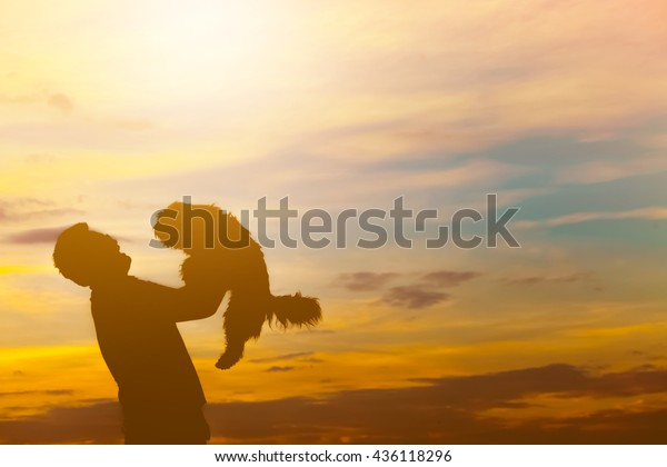Silhouette of happy man and dog over beautiful twilight sunset.