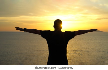 Silhouette of happy man open arms under the sunset