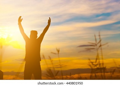 Silhouette of happy man over beautiful twilight sunset.