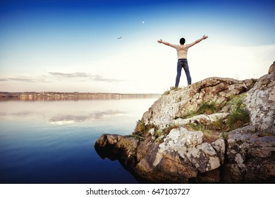 Silhouette of  happy man standing on  rock and arms outstretched against the sky. freedom