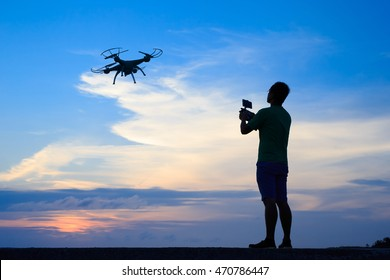 Silhouette of Happy man use drones outdoor with sunset, male