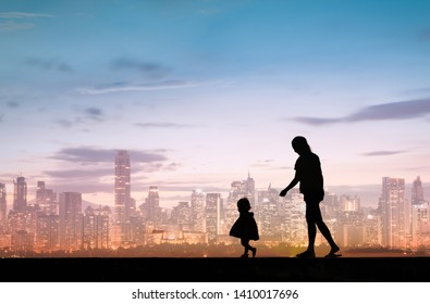 Silhouette of happy mother and child walking in the city.