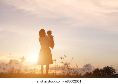 silhouette Happy mother and daughter laughing together outdoors