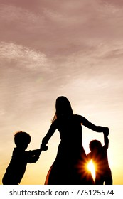 A silhouette of a happy mother and her two little boy children holding hands and dancing outside at sunset.