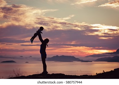 Silhouette of a happy mother,  plays with toddler child and lifts him over her head outside, isolated against the sunset, ocean, fjords and mountains in fog. North Norway, Lofoten Islands, Scandinavia